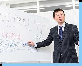 写真:ホワイトボードに向かって営業研修を指導