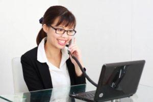 写真:電話応対をしている眼鏡をかけた笑顔の女性