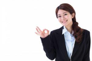 写真:オッケーサインをしている笑顔の女性