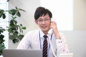 写真:笑顔で電話応対をしている眼鏡をかけた男性