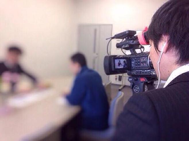 写真:ビデオカメラを構えた男性
