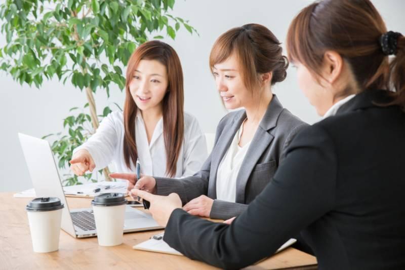 写真:ノートパスコンを指さしている女性3人